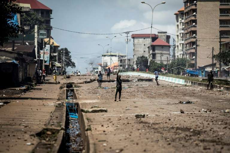 a group of people walking on a beach: Opposition leader Cellou Dalein Diallo's self-proclaimed victory at Guinea's presidential election on October 18, 2020 led to a week of clashes between supporters and security forces across the West African nation (Conakry pictured October 23, 2020)