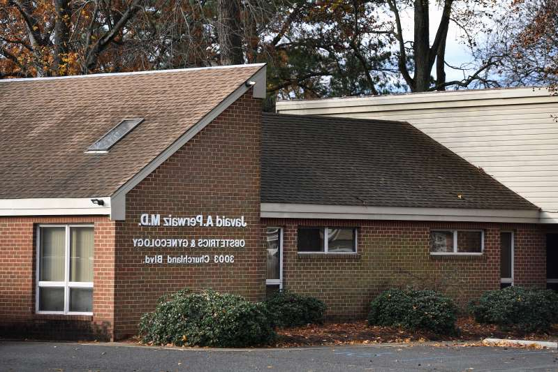 a house with trees in front of a brick building: Chesapeake, Va., offices where Javaid Perwaiz used to work, seen in December. He has been accused of performing unnecessary surgeries.