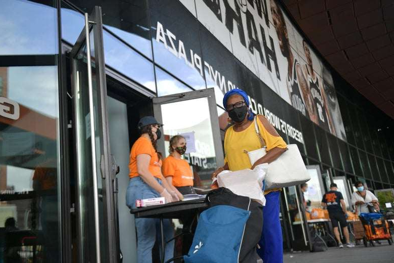 a man sitting in front of a building: New Yorkers in need receive free produce during a Pop-Up Food pantry event hosted by Food Bank For New York City at the Barclays Center on September 10, 2020. Michael Loccisano/Getty Images