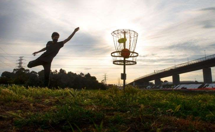a man standing on a bridge over a body of water: The Age, News. Frisbee disc golf is growing in popularity during the pandemic because it is a non-contact sport. Pic shows Oscar Felhberg. Pic Simon Schluter 14 October 2020