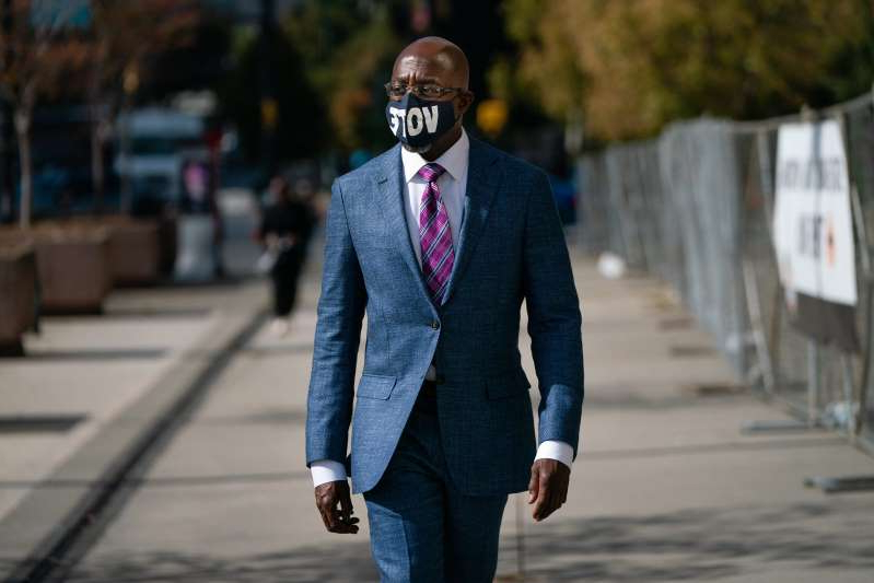 a man wearing a suit and tie walking down the street: Raphael Warnock has seen a jump in the polls for his U.S. Senate candidacy thanks in part to support from WNBA players.