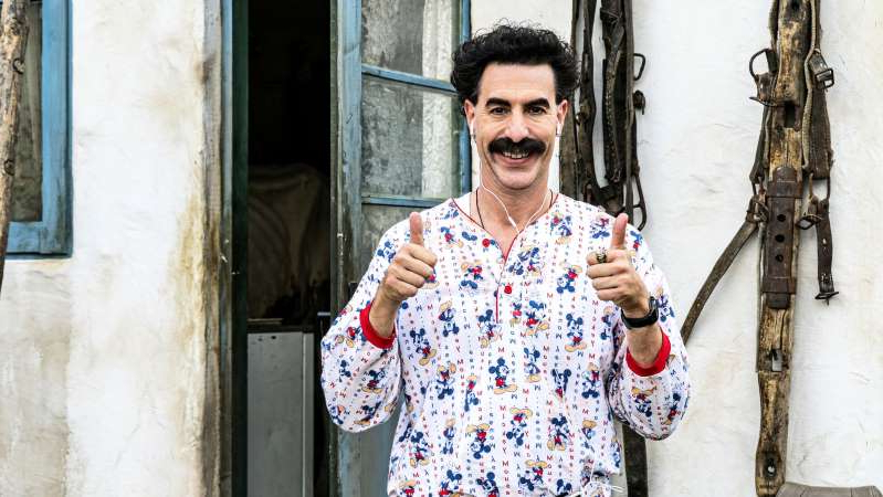 a person standing in front of a building talking on a cell phone: The American Conservative Union has threatened legal action over a scene in 'Borat 2' which sees Sacha Baron Cohen wearing Ku Klux Klan robes.