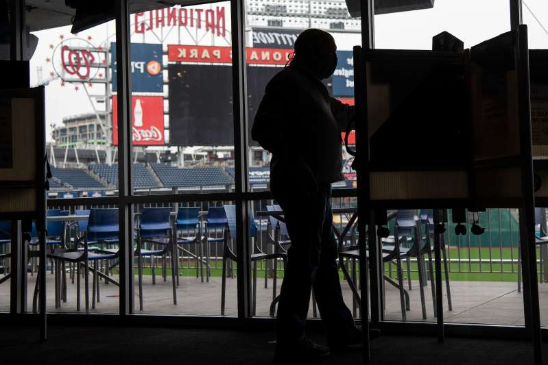a person standing next to a fence: Mark Fischer helps set up an early voting center in the PNC Diamond Club at Nationals Park on Monday.