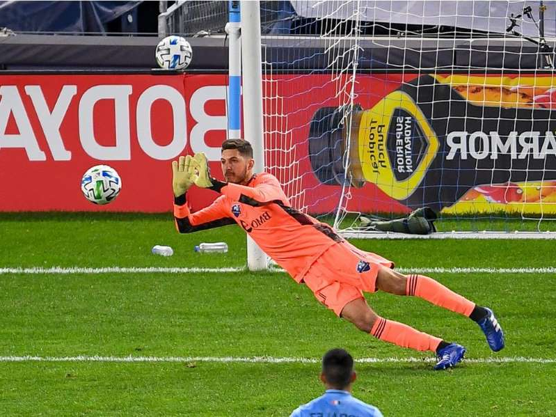 a person with a football ball on a field: Impact goalkeeper James Pantemis makes a save against New York City during MLS game at Yankee Stadium on Oct. 24.
