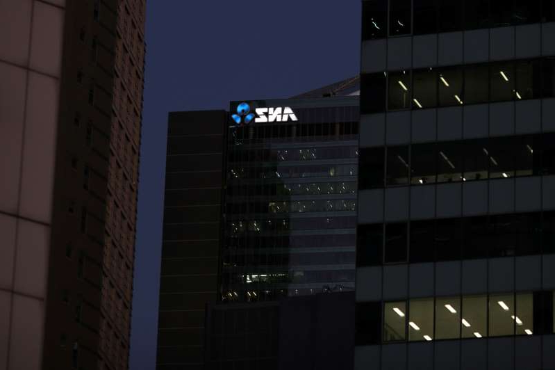 a tall building lit up at night: Office buildings and the ANZ logo are seen in Sydney
