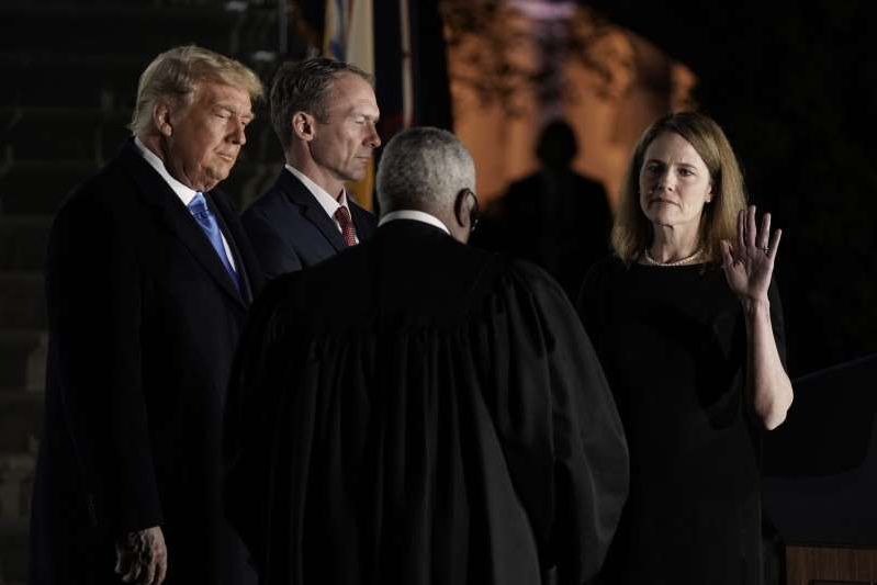 Donald Trump wearing a suit and tie talking on a cell phone: Clarence Thomas, center, administered the judicial oath to Amy Coney Barrett, at the White House in Washington, D.C., on Oct. 26.