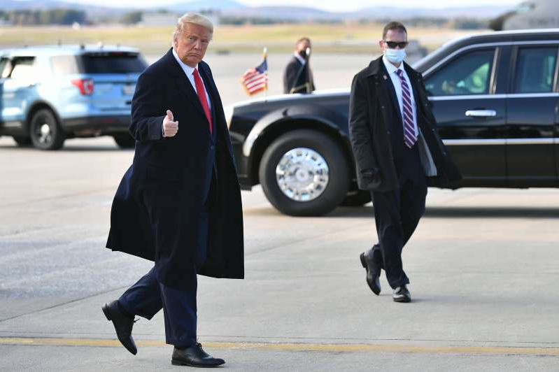 Donald Trump wearing a suit and tie walking down the street: US President Donald Trump steps off Air Force One upon arrival at Bangor International Airport in Bangor, Maine on October 25, 2020