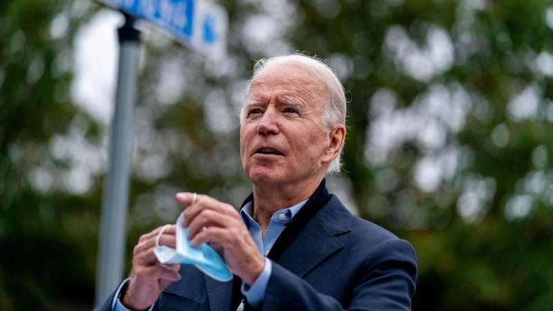 Joe Biden talking on a cell phone: Democratic presidential candidate former Vice President Joe Biden holds his mask as he speaks to members of the media outside a voter service center, Oct. 26, 2020, in Chester, Pa.