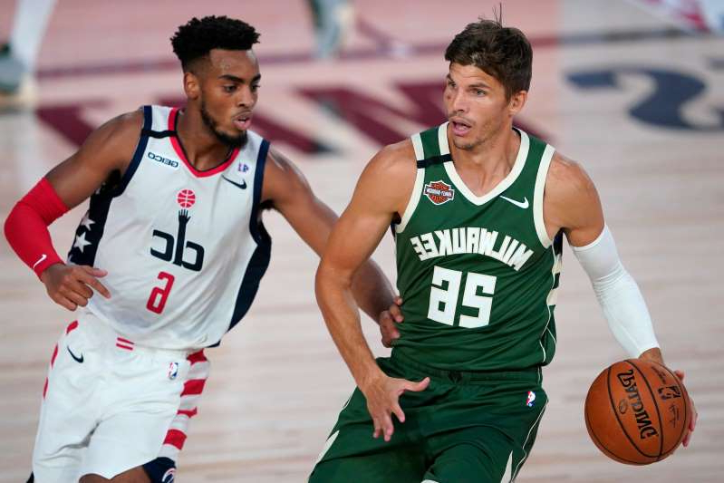 Kyle Korver holding a basketball: Milwaukee Bucks' Kyle Korver (26) looks to pass while covered by Washington Wizards' Troy Brown Jr. (6) during the first half of an NBA basketball game, Tuesday, Aug. 11, 2020, in Lake Buena Vista, Fla. (AP Photo/Ashley Landis, Pool)