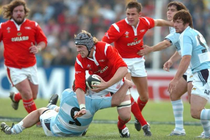 Lee Byrne et al. playing football on a field: Alun Wyn Jones on his Test debut for Wales against Argentina in June 2006