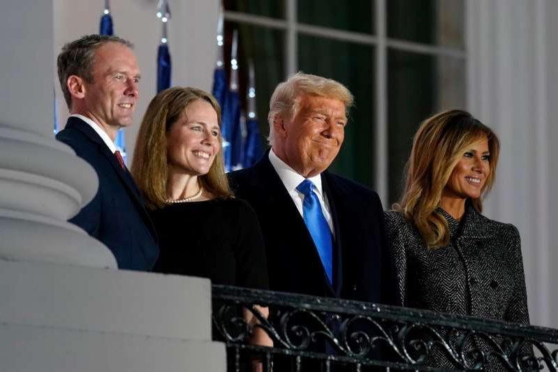 Melania Trump et al. wearing a suit and tie: From left, first lady Melania Trump, President Donald Trump, Amy Coney Barrett and Jesse Barrett, stand on the Blue Room Balcony after Supreme Court Justice Clarence Thomas administered the Constitutional Oath on the South Lawn of the White House in Washington on Monday.