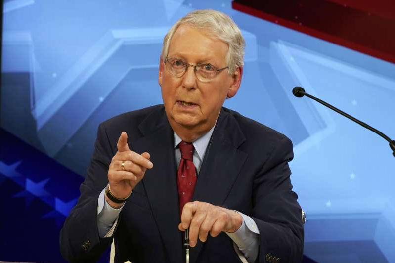 Mitch McConnell wearing a suit and tie: Senate Majority Leader Mitch McConnell (R-KY) speaks during a debate with Democratic challenger Amy McGrath on October 12, 2020 in Lexington, Kentucky.