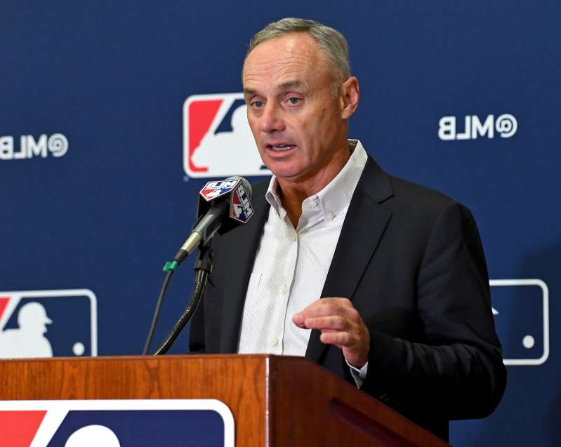 Rob Manfred holding a sign: MLB commissioner Rob Manfred painted a troubling picture of the league's COVID-19-related revenue losses.