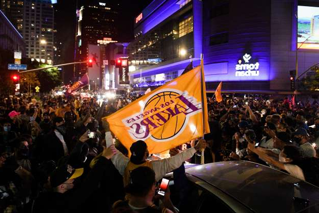 Slide 1 of 10: Lakers fans celebrate the franchise's NBA championship in the streets of Los Angeles on Sunday night.