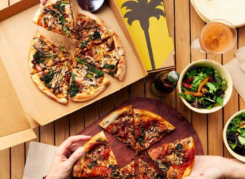 a box of pizza sitting on top of a wooden table: california pizza kitchen pizza