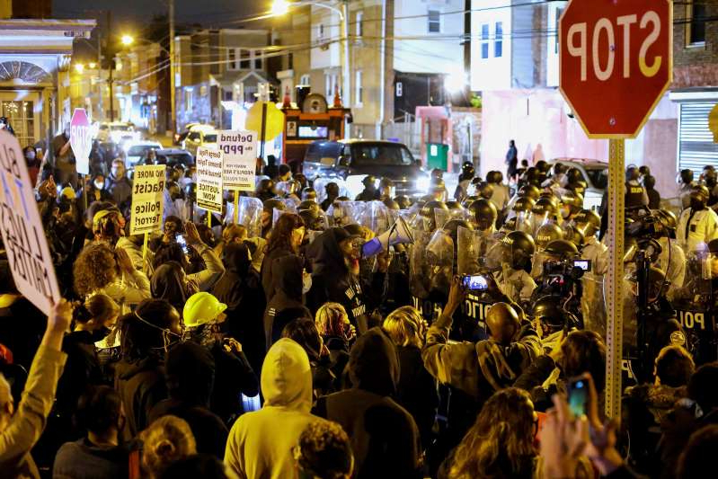 a group of people standing in front of a crowd: PHILADELPHIA, PA - OCTOBER 27: Demonstrators protest the fatal police shooting of Walter Wallace Jr. on October 27, 2020 in Philadelphia, Pennsylvania. Wallace Jr. was fatally shot by two Philadelphia police officers after refusing to drop a knife he was holding. (Photo by Joshua Lott/The Washington Post)