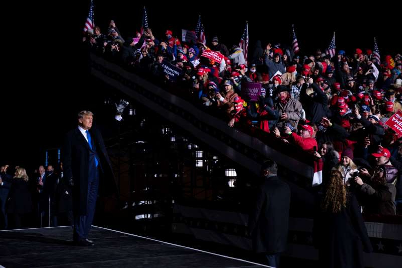 a group of people standing in front of a crowd: President Donald Trump waves after speaking during a campaign rally at Eppley Airfield, Tuesday, Oct. 27, 2020, in Omaha (AP Photo/Evan Vucci)