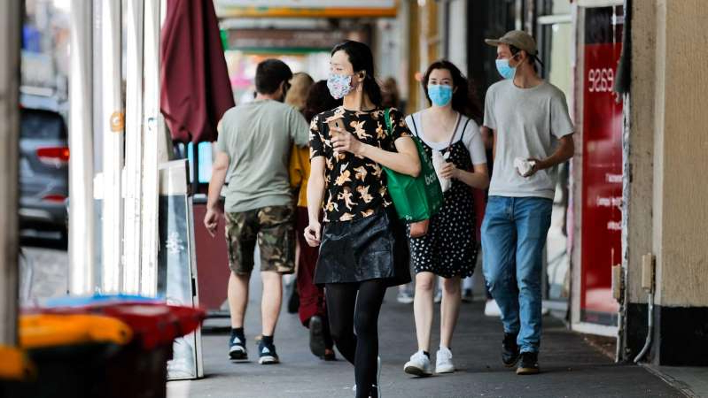a group of people walking down the street: Melbourne's 14-day rolling average of new coronavirus cases has been steadily falling during October. (ABC News: John Graham)