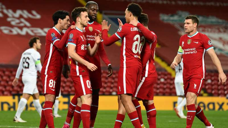 a group of young men playing a game of football: Diogo Jota is congratulate after scoring Liverpool's 10,000th goal.