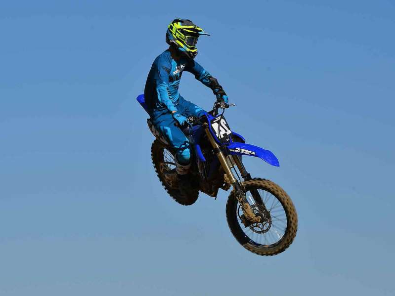 a man flying through the air while riding a motorcycle down a dirt road: Riding the 2021 Yamaha YZ250F at State Fair MX in Perris, California.