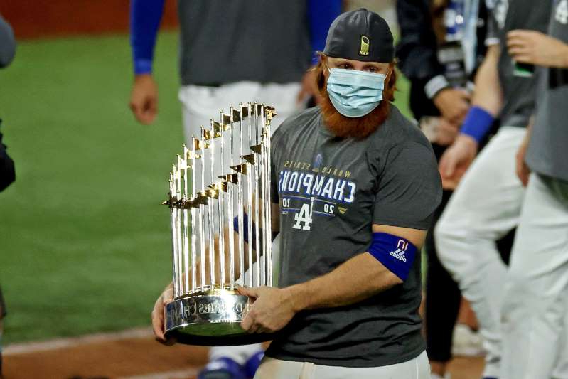 a man holding a baseball bat: Los Angeles Dodgers third baseman Justin Turner celebrates with the Commissioner's Trophy after winning the World Series.