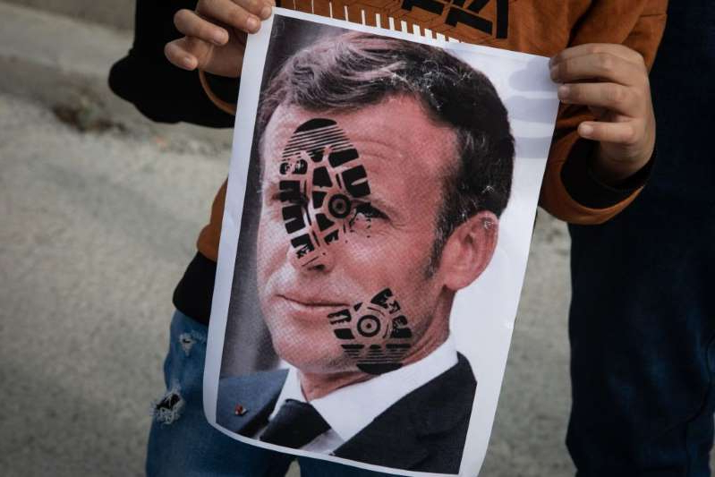 a man holding his head in his hands: ISTANBUL, TURKEY - OCTOBER 25: A boy holds a poster showing the portrait of French President Emmanuel Macron during a protest against French president Emmanuel Macron on October 25, 2020 in Istanbul, Turkey. People gathered to protest against the recent statements by French President Emmanuel Macron regarding the beheading of a teacher that displayed cartoons of Prophet Muhammad in his class and the closure of some mosques in France. (Photo by Chris McGrath/Getty Images)