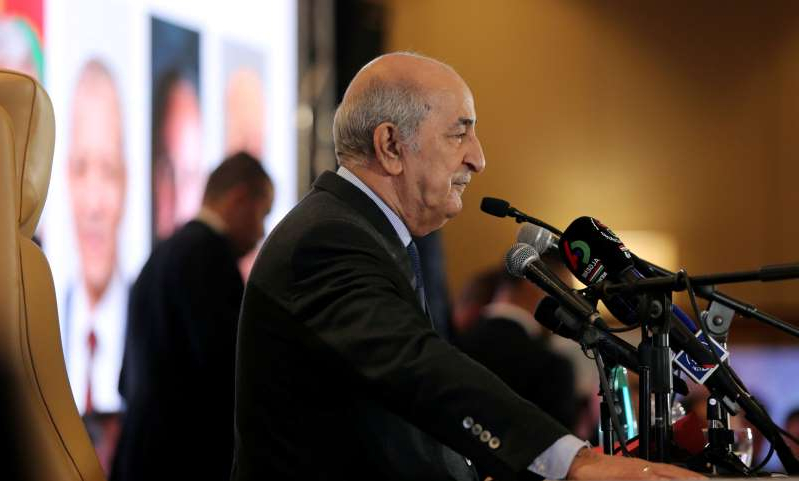 a man standing in front of a microphone: Tebboune, 75, said on Saturday he was self isolating after several senior aides tested positive for the coronavirus [File: Ramzi Boudina/Reuters]