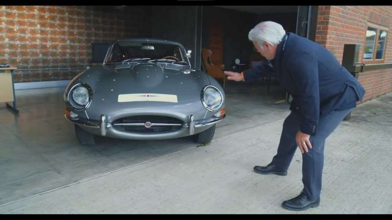 a man standing next to a car: Frank Stephenson E-Type