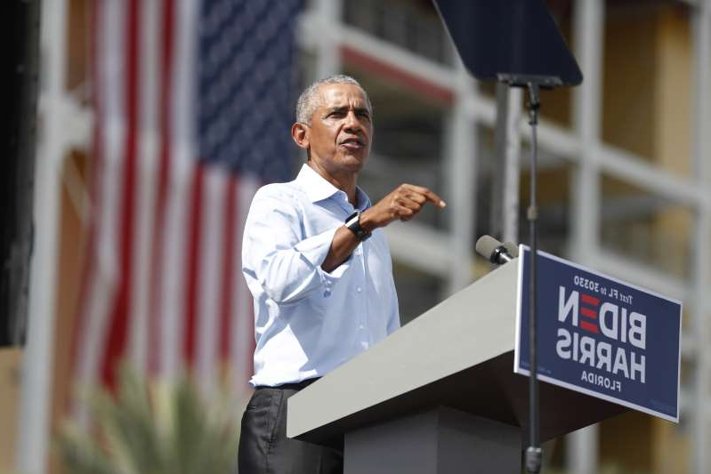 Barack Obama standing in front of a building: Former President Barack Obama speaks during a campaign event for Democratic presidential nominee Joe Biden in Orlando, Florida on October 27, 2020.