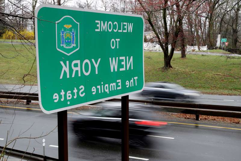 FILE - In this Sunday, March 29, 2020, file photo, a sign welcomes motorists to New York, on the border with Connecticut, near Rye Brook, N.Y. Governors in New York's tri-state region were left scrambling in late October 2020 when virus infection rates in Connecticut and New Jersey climbed high enough to qualify for their own 14-day quarantine requirements. It highlighted a worrying trend in a region that used the list to set itself apart from large swaths of the country and raised questions about whether it was worth keeping. (AP Photo/Seth Wenig, File)