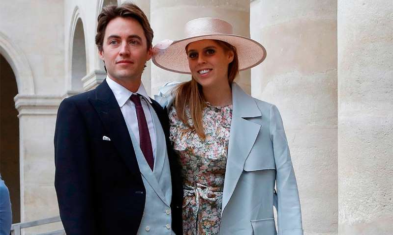 Princess Beatrice of York wearing a suit and tie standing in front of a building: Hello! Magazine