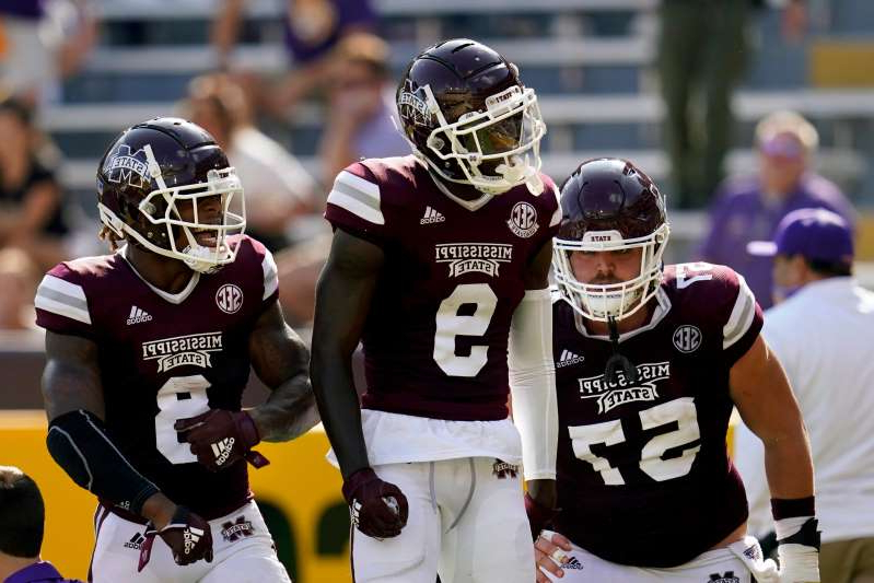 a baseball player holding a bat: Mississippi State wide receiver Tyrell Shavers (9) celebrates his touchdown reception with running back Kylin Hill (8) and offensive lineman Cole Smith (57) in the first half against LSU, Saturday, Sept. 26, 2020.