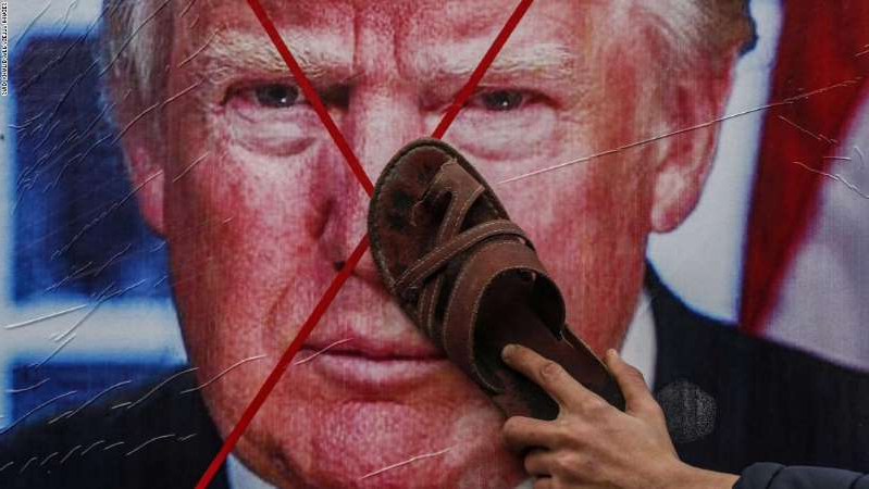 a close up of a man with his mouth open: A Palestinian protester holds his sandal against a poster depicting US President Donald Trump during a demonstration against Trump's Middle East peace proposal in Khan Yunis, in the southern Gaza Strip, on February 3, 2020.