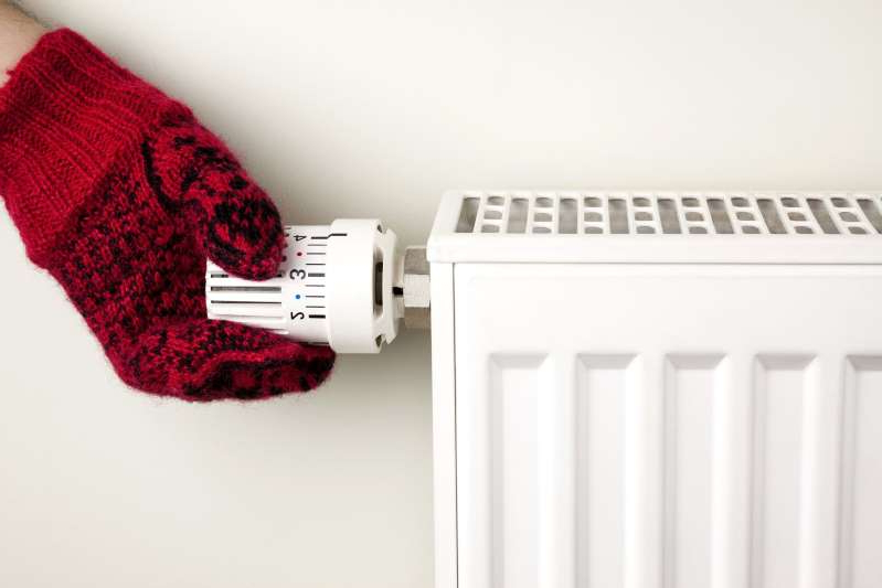 a close up of a toy: Person wearing a mitten adjusting a radiator thermostat.