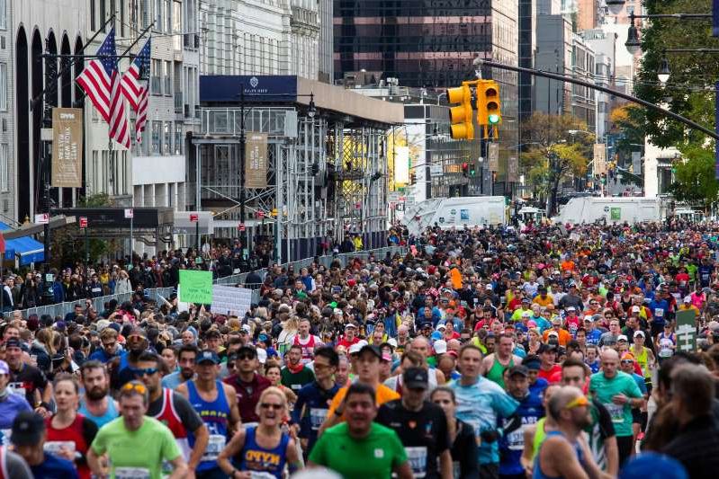 a group of people standing in front of a large crowd of people: Because the 2020 New York City Marathon is a virtual event, it won't have the usual 50,000 participants running through the city's five boroughs.
