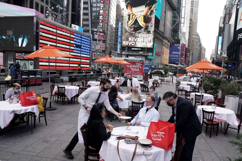 "a group of people walking down a street: Servers deliver food to a table at a pop-up restaurant set up in New York's Times Square for ""Taste of Times Square Week"" on Oct. 23. (Carlo Allegri/Reuters)"