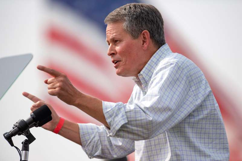 a man holding a microphone: Sen. Steve Daines speaks to a crowd of supporters Sept. 14 at a Republican campaign rally in Belgrade, Mont.