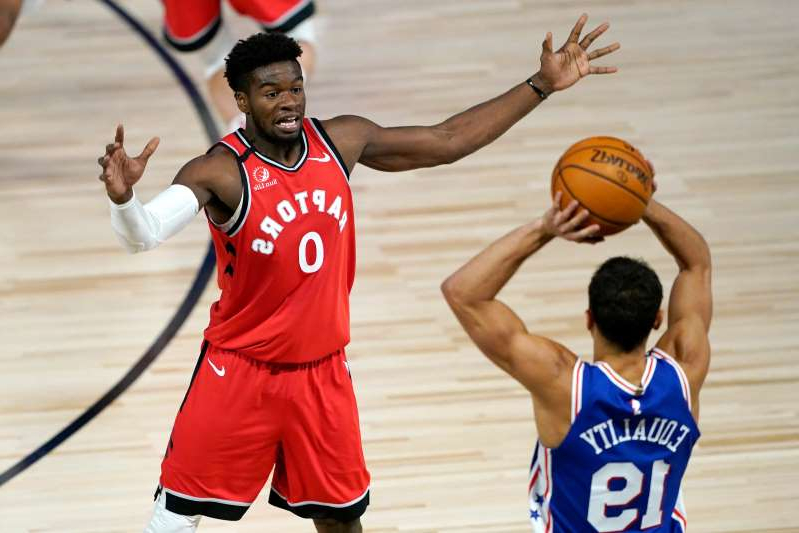 a man playing a game of basketball: The Raptors' Terence Davis defends during a game against the 76ers in August.