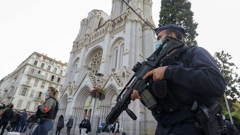 a man standing in front of a building: Police officers stand guard on October 29, 2020, after a knife-wielding man killed three people at the Notre-Dame de l'Assomption Basilica in Nice, France.