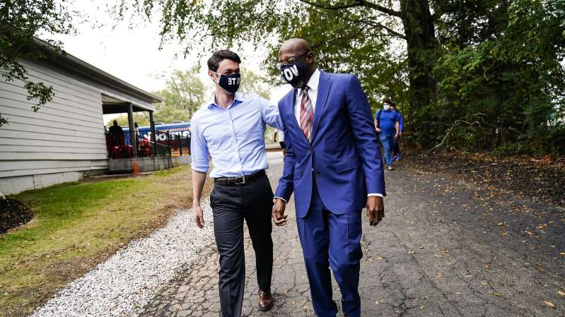 a man standing on a dirt road: Democratic candidates for Senate Rev. Raphael Warnock (left) and Jon Ossoff arrive for a campaign event in Jonesboro, Georgia, on October 27. The two are hoping to unseat incumbent Sens. David Perdue and Kelly Loeffler.