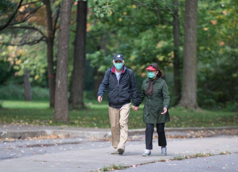 a person walking down the street: People wear face masks as they walk through a park in Montreal, Thursday, October 1, 2020, as the COVID-19 pandemic continues in Canada and around the world.