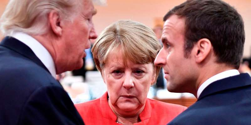 Angela Merkel standing in front of a crowd: French President Emmanuel Macron, German Chancellor Angela Merkel, and US President Donald Trump at the G20 meeting in Hamburg, Germany, in July 2017. JOHN MACDOUGALL/AFP via Getty Images