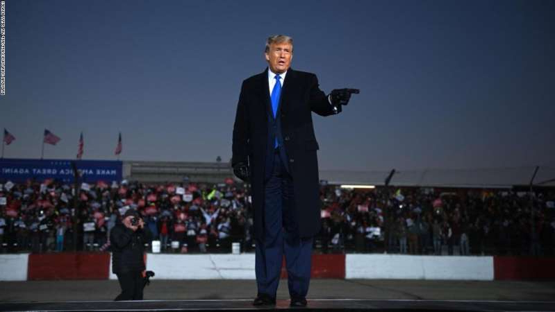 Donald Trump wearing a suit and tie standing in front of a crowd: US President Donald Trump gestures as he arrives for a Make America Great Again rally at the La Crosse Fairgrounds Speedway, October 27, 2020, in West Salem, Wisconsin. (Photo by Brendan SMIALOWSKI / AFP) (Photo by BRENDAN SMIALOWSKI/AFP via Getty Images)