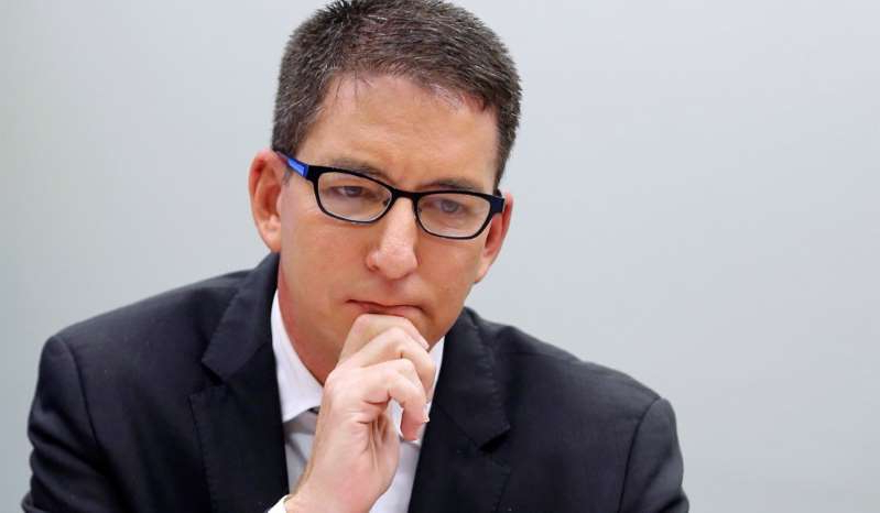Glenn Greenwald wearing glasses and a suit and tie: Glenn Greenwald attends a meeting of the human rights committee of the Chamber of Deputies in Brasilia, Brazil, June 25, 2019.