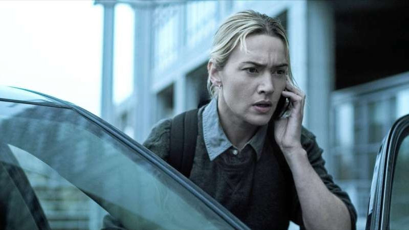 Kate Winslet talking on a cell phone in front of a window: Kate Winslet in