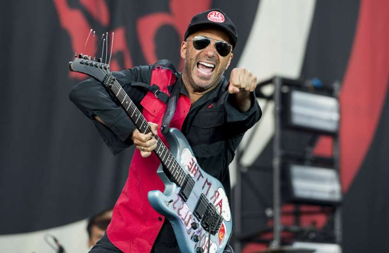 Tom Morello wearing a helmet and holding a guitar