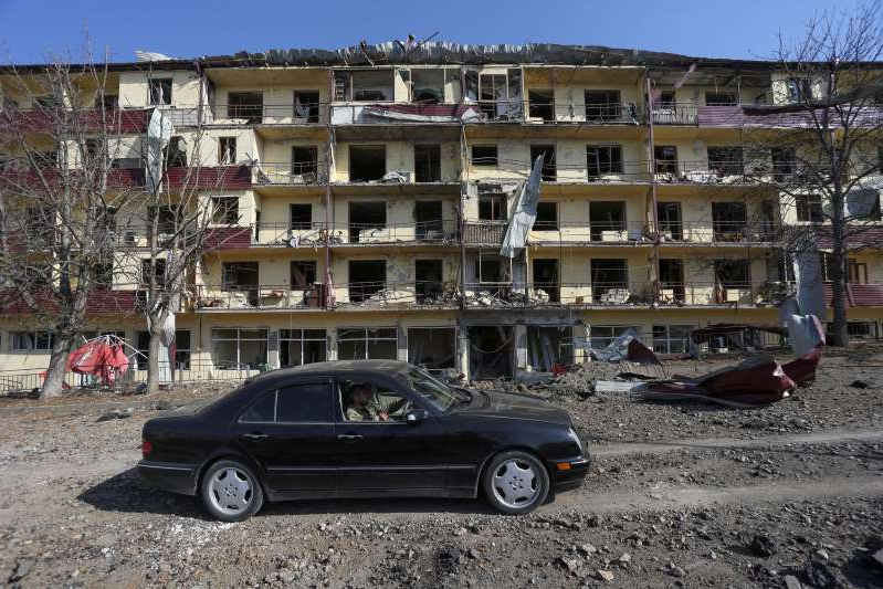 a car parked in front of a building: A man drives a car past a damaged building on Oct. 29, following recent shelling in the breakaway region of Nagorno-Karabakh. (Vahram Baghdasaryan/Photolure/Reuters)
