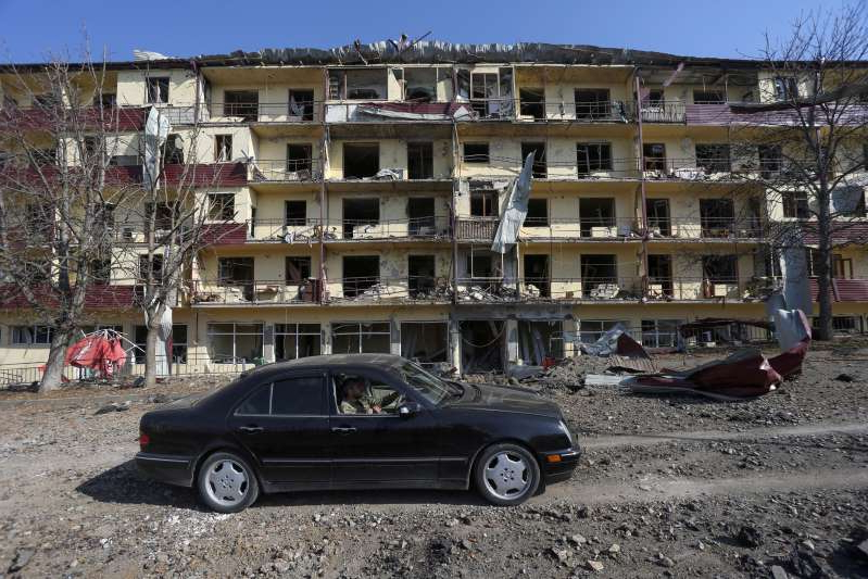 a car parked in front of a building: A view shows a damaged building following recent shelling in Shushi