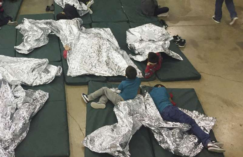 a group of clothes on a bed: Children rest on the floor beneath aluminum-foil blankets at a U.S. Customs and Border Protection detention facility in McAllen, Tex., on June 17, 2018 (U.S. Customs and Border Protection's Rio Grande Valley Sector via AP)