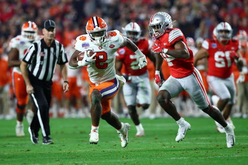 a group of football players on the field: Clemson running back Travis Etienne breaks free to scores a touchdown against Ohio State during the 2019 Fiesta Bowl at State Farm Stadium.